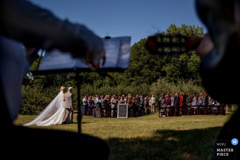 Photo of the bride walking with her father toward the ceremony as musicians play outside by a Chicago, IL wedding photographer.