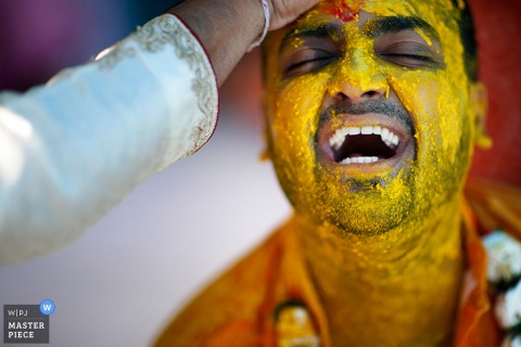 Photo of the groom smiling with his eyes closed as someone applies haldi to his face by a Paris, France wedding photographer.
