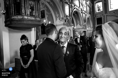 The bride and her father look at each other as the groom kisses the father of the bride's cheek in this black and white photo by a Lecce wedding photographer.