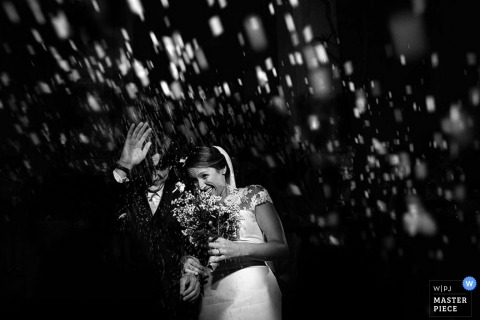 Black and white photo of the bride and groom walking together as rice falls around them by a Lecce, Italy wedding photographer.