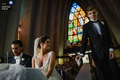 Photo of a young man standing next to the bride and groom as they kneel at the altar by a Madrid, Spain wedding photographer.