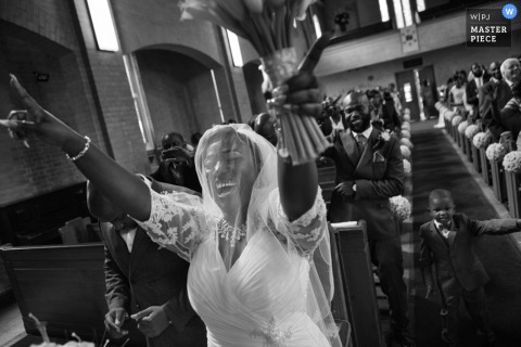 Black and white photo of the bride walking down the aisle smiling with her hands in the air by a London, England wedding reportage photographer.