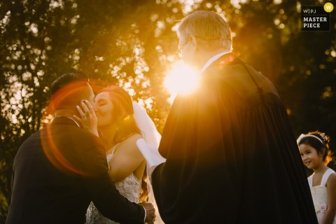 Photo of the bride and groom kissing at the alter as the sun shines through the trees behind them by a Washington, D.C. wedding photographer.