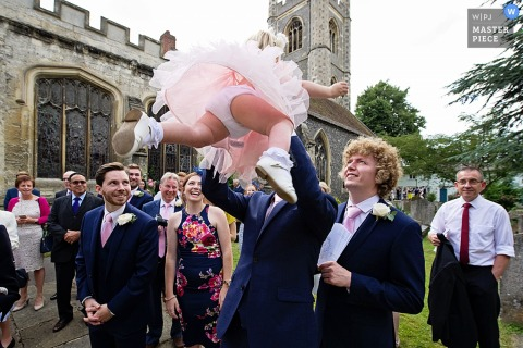 Photo of a man lifting a little girl into the air as other guests watch by a Devon, England wedding reportage photographer.