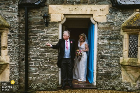 Photo of the bride preparing to exit a stone building by a North Yorkshire, England wedding reportage photographer.