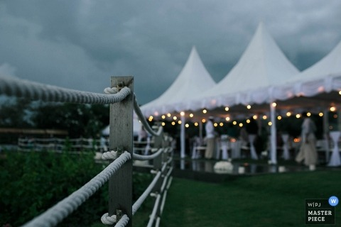 Photo of guests beneath the reception tent with a gray sky overhead by a Bali, Indonesia wedding photographer.