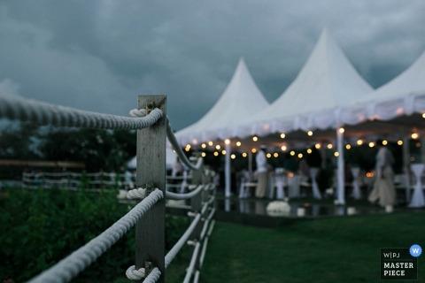 Foto von Gästen unter dem Empfangszelt mit einem grauen Himmel obenliegend von einem Hochzeitsfotografen Balis, Indonesien.