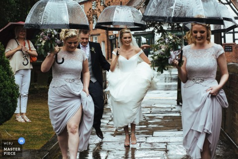 The bride and her bridesmaids hold their dresses up as they walk through the rain with umbrellas by a London wedding reportage photographer.