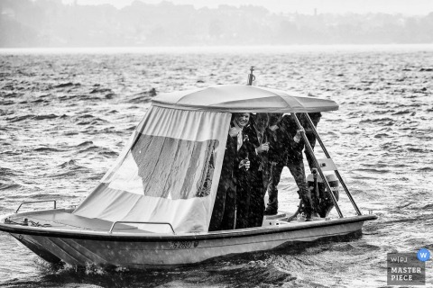 Black and white photos of guests trying to shield themselves from the rain on a small boat by a Switzerland wedding photographer.