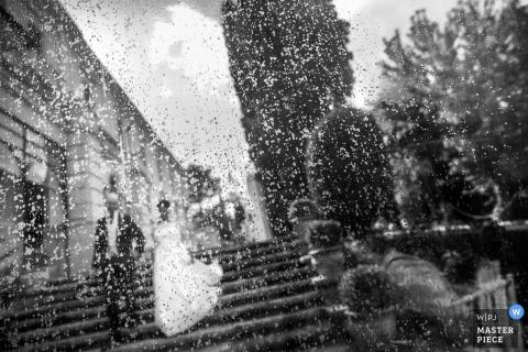 Foto van de bruid en de bruidegom die een vlucht van steentreden dalen die door een rain-covered venster door een het huwelijksfotograaf van Calabrië wordt genomen.
