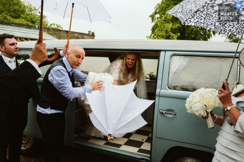 Guests help the bride out of her vehicle as she opens a white umbrella in this photo by a Greater Manchester, England wedding reportage photographer.