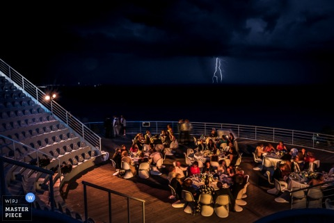 Photo of the guests sitting outside at night during the reception as lightning flashes in the background by a France wedding photographer.