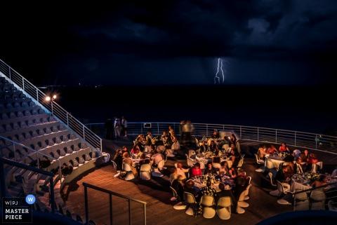 Foto van de gasten die buiten zitten 's nachts tijdens de receptie als bliksem flitst op de achtergrond door een huwelijksfotograaf uit Frankrijk.