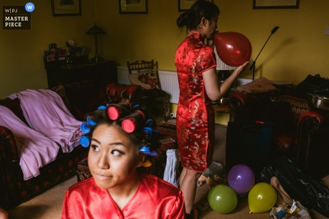 Photo of the bride getting ready as a woman blows up balloons by a North Yorkshire, England wedding reportage photographer.