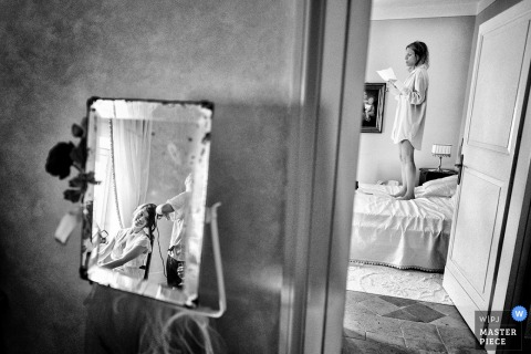Black and white photo of a woman standing on a bed while the bride, reflected in a mirror, gets her hair done in the other room by a Tuscany wedding photographer.