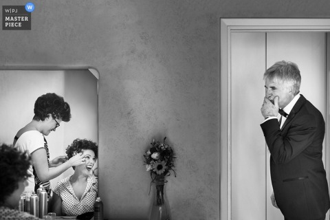 Black and white photo of a man tearing up as he watches the bride getting her hair done by an Umbria wedding photographer.