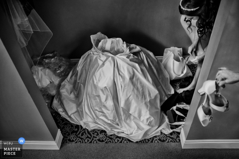 Foto in bianco e nero del vestito della sposa sul pavimento pronto per lei per entrare come una donna le mani la sposa le sue scarpe da un fotografo di matrimoni Charleston, SC.