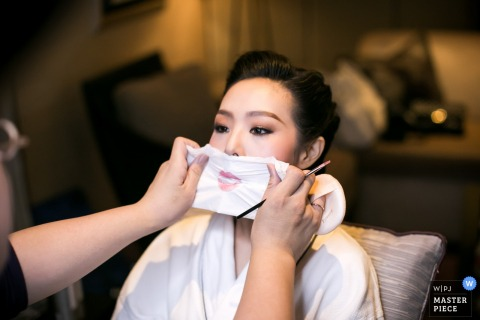 Photo de la maquilleuse épongeant le rouge à lèvres de la mariée sur cette photo prise par un photographe de reportage de mariage à Londres.