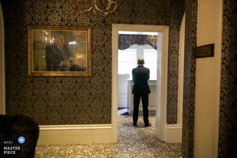 Photo of a man standing alone in an ornate room by a London, England wedding reportage photographer.