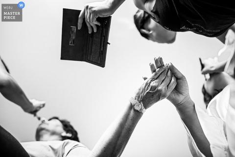Foto de detalle en blanco y negro de la novia que sostiene la mano de una mujer, ya que ambas se maquillan por un fotógrafo de bodas de Nueva Jersey