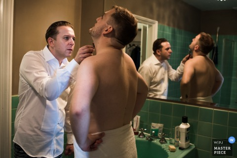 A man helps another shave his face before the ceremony in this photo by a Kent wedding reportage photographer.