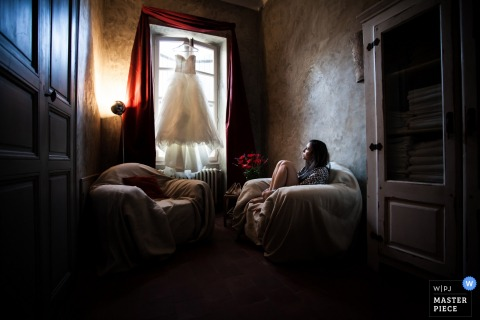 Photo of the bride sitting in a chair and looking up at her wedding dress hanging in the window by a Miami, FL wedding photographer.