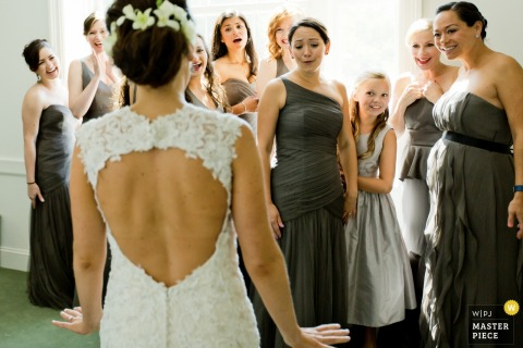 The bridesmaids look at the bride in awe of her wedding dress in this photo by a Jersey City, NJ wedding photographer.