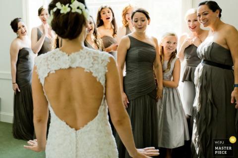 Die Brautjungfern betrachten die Braut in Ehrfurcht vor ihrem Hochzeitskleid auf diesem Foto eines Hochzeitsfotografen aus Jersey City, NJ.