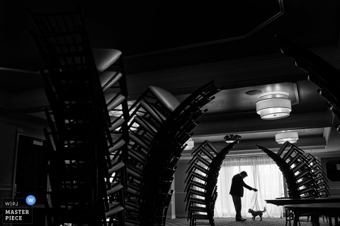 Black and white photo of a man and cat in the distance taken through large stacks of chairs in the reception hall by a Lake Tahoe, CA wedding photographer.