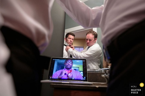 Photo of two men watching a video on how to tie a bow tie as they help each other get ready by a Chicago, IL wedding photographer.