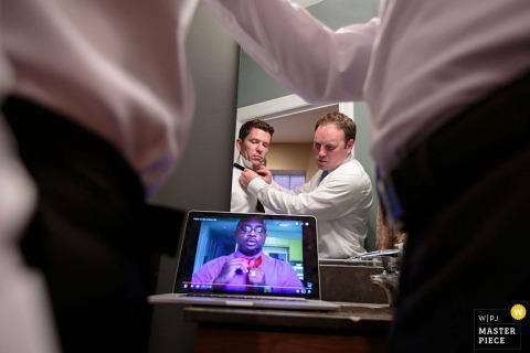 Foto di due uomini che guardano un video su come legare un papillon mentre si aiutano a vicenda a prepararsi da un fotografo di matrimoni di Chicago, IL.