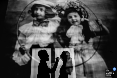 Black and white photo of the bride getting her makeup done reflected in a picture of a young boy and girl by a Madrid, Spain wedding photographer.