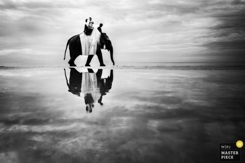 Foto en blanco y negro de un hombre montado en un elefante reflejado en el agua por un fotógrafo de bodas en Phuket, Tailandia.