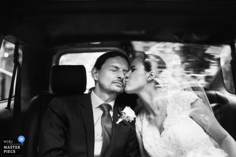 Foto in bianco e nero della sposa che bacia lo sposo sulla guancia nella parte posteriore di una macchina da un fotografo di matrimoni di Brooklyn, NY.