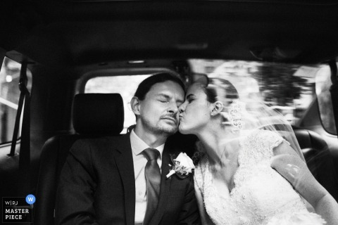 Black and white photo of the bride kissing the groom on the cheek in the back of a car by a Brooklyn, NY wedding photographer.