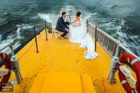 Photo of the bride and groom sitting on a boat with a bright yellow floor by a Netherlands wedding photographer.