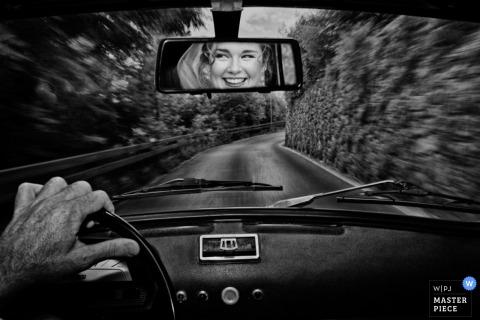 Fotografía en blanco y negro tomada dentro de un vehículo mientras conduce por la carretera con el rostro de la novia reflejado en el espejo retrovisor por un fotógrafo de bodas de Florencia, Toscana.
