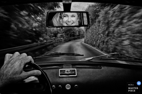Black and white photo taken inside a vehicle as it drives down the road with the bride's face reflected in the rear view mirror by a Florence, Tuscany wedding photographer.