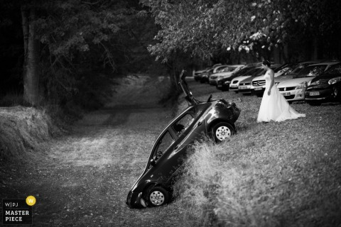 Black and white photo of the bride looking at a car that has fallen over a hill by a Miami, FL wedding photographer.