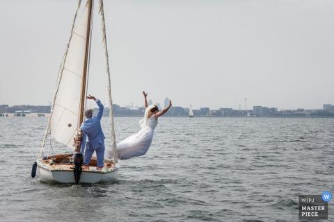 Prankfoto van de 'bruid' die van een zeilboot in haar trouwjurk springt door een Amsterdamse huwelijksfotograaf.