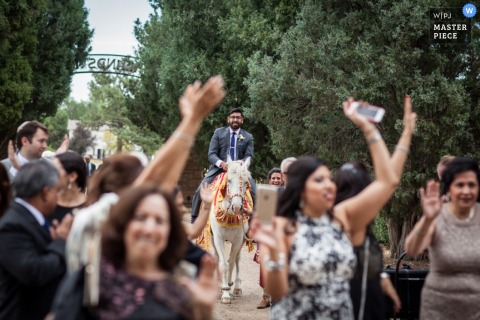 Photo of guests walking outside as the groom rides a white horse behind them by a Montana wedding photographer.
