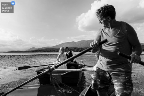 Black and white photo of a man rowing a boat looking behind him at the bride and groom kissing in theirs by a Lombardy wedding photographer.