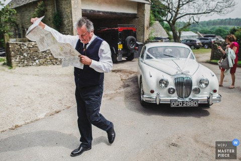 Photo of a man checking a map as he stands outside of a vintage car by a Derbyshire wedding reportage photographer.