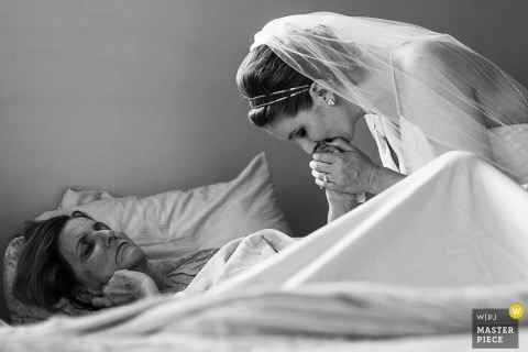 Black and white photo of the bride kissing a woman's hand as she lays in bed by a San Francisco, CA wedding photographer.