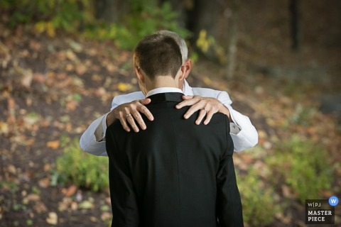 Photo taken from behind of a man putting his hands on the groom's shoulders by an Atlanta, GA wedding photographer.