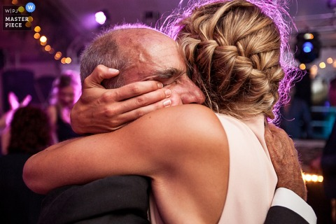 Photo of the bride hugging a man during the reception by a Paris, France wedding photographer.