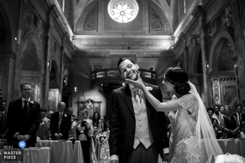 Black and white photo of the bride tilting the groom's head during the ceremony as guests watch by a Rome wedding photographer.