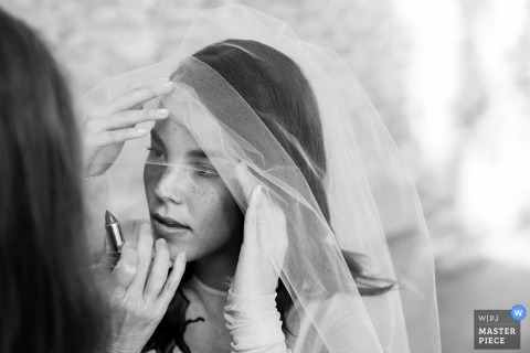 Black and white photo of a woman helping the bride with her lipstick by a Hudson Valley, NY wedding photographer.