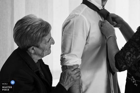 Black and white photo of a woman helping a man with his tie as another holds his arm affectionately by a Valencia, Spain wedding photographer.