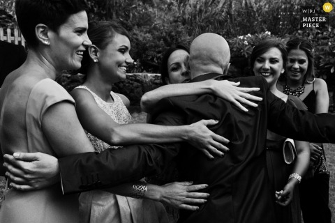 Black and white photo of a group of women hugging a man by a Madrid, Spain wedding photographer.